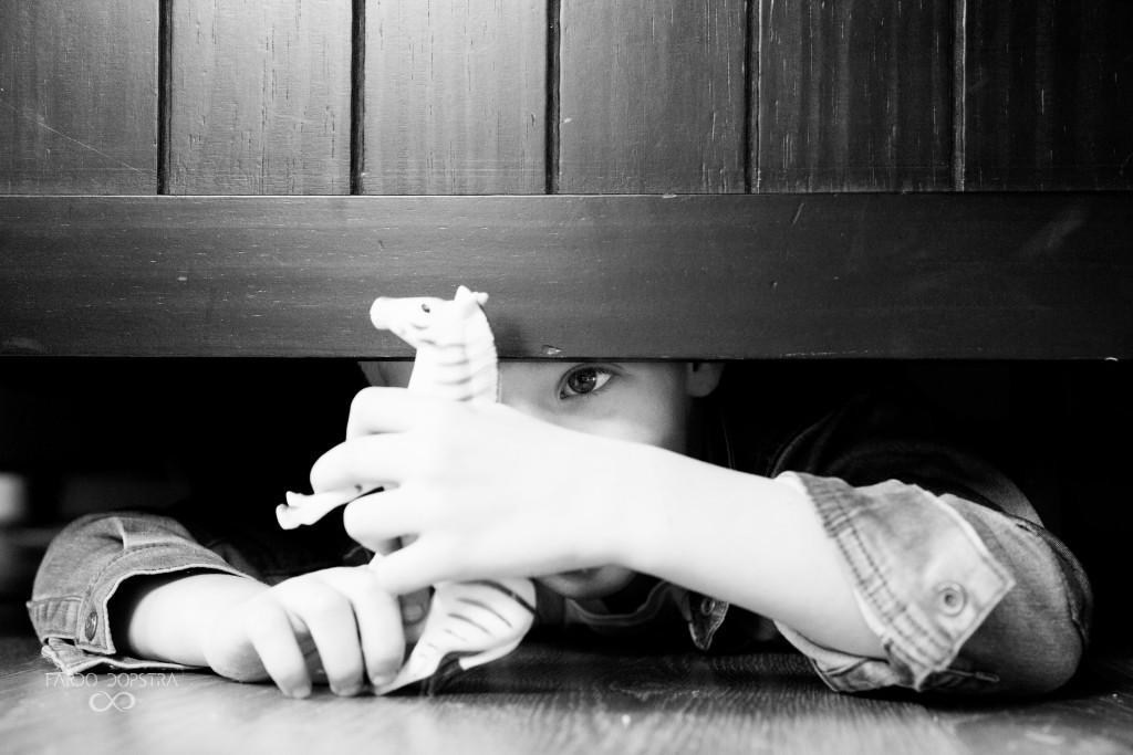 De mooiste foto's maak ik van kinderen als ze gewoon aan het spelen zijn, zoals Roan hier. Onder het bed is een hele wereld waar grote mensen niets meer van weten.