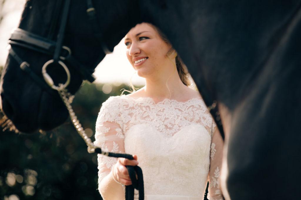 bruid in bruidsjurk met kant, en de hals en neus en borst van haar Friese paard