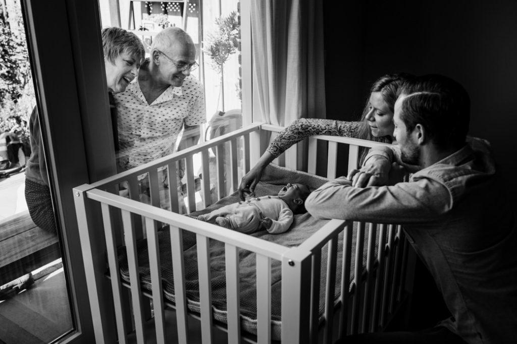 Grootouders kijken door het raam naar hun kinderen en kleinkinderen
